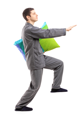 Full length portrait of a man in pajamas sleepwalking with a pil